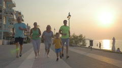 Friendly family running to finish on the pavement at sunset Stock Footage