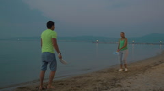 Man and woman playing badminton on seacoast Stock Footage