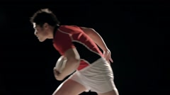 Slow motion footage of Japanese rugby player running with ball against black - stock footage