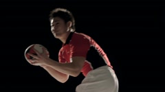 Slow motion footage of Japanese rugby player receiving ball against black - stock footage