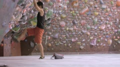 Japanese athlete climbing a wall in a bouldering gym - stock footage