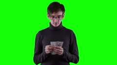 Young rich businessman with money, counting dollars on chromakey - stock footage