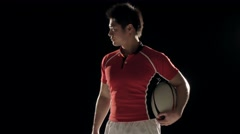 Waist-up portrait of Japanese rugby player holding the ball on black background Stock Footage