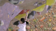 Close up of Japanese athlete climbing a wall in a bouldering gym - stock footage