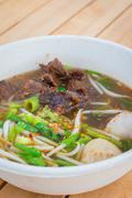 Noodle soup with beef in thai or chinese style on table background - stock photo