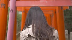 Slow motion footage of Japanese young woman walking through red Torii gates at a Stock Footage