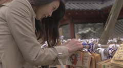 Japanese young woman with Ema votive tablet at the temple Stock Footage