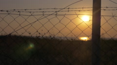Beautiful sunset seen through barbed wire Stock Footage