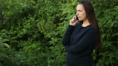 beautiful girl talking on the phone in the park among the trees - stock footage