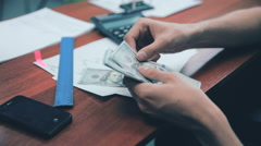 Businessman counting money US dollars on his workplace in office Stock Footage