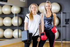Portrait of two women at boxing training in fitness gym Stock Photos