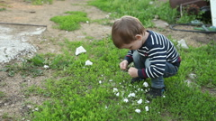 Little boy playing outdoors squatting Stock Footage
