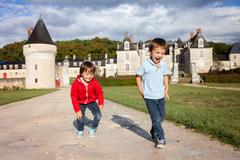 Two boys, happily playing after the rain on the driveway of French Gizeux cas - stock photo