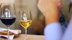 A couple on a restaurant drink wine and eat entries. Stock Footage