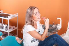 Young beautiful girl is preparing for prosthetic dentistry. Keeps false teeth Stock Photos