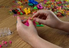 children's hands are weaving figures out of colored rubbers - stock photo
