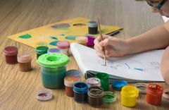 child's hands drawing in album with colored inks - stock photo