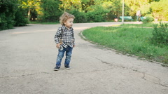Curly little boy running in the park. He is very cute and funny - stock footage