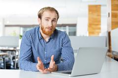 Serious businessman with laptop sitting and talking in office - stock photo