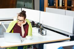 Businesswoman working with laptop and feeling cold in office Stock Photos