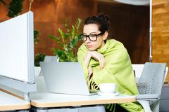 Beautiful thoughtful woman using laptop and feeling cold on workplace Stock Photos