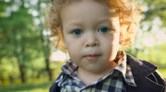 Portrait of a happy boy in the park malenkovo. Curious children with curly blond Stock Footage