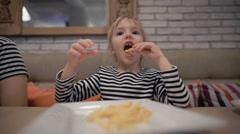 Cute little baby girl sitting at cafe eating delicious french fries Stock Footage