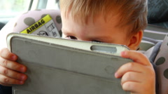 Little boy using a tablet sitting in a car seat car Stock Footage