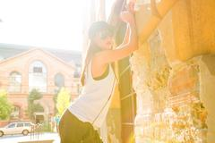 Hip hop girl with headphones in a urban environment - stock photo