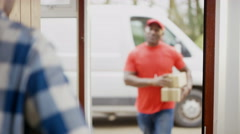 4K Portrait of smiling delivery driver bringing packages to customer's door. Sho Stock Footage