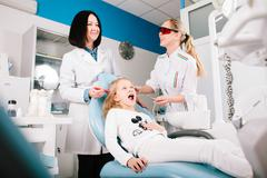 Young handsome dentist treats tooth child, a woman dentist Stock Photos