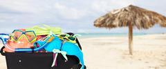 Suitcase with bikini and sunglasses. - stock photo