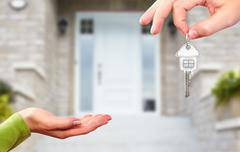 Hand with a key over new house background. Stock Photos