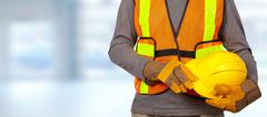 Worker with helmet in orange security vest. Stock Photos