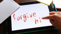 Forgive him, hands writing words on tablet, forgiveness concept - stock footage