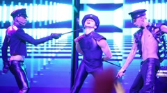 Three dancers of Kazaky band with police cap are dancing on stage Stock Footage