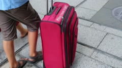 Boy is holding handle of the luggage and going on a street. Stock Footage