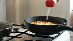 Dish with macaroni is heated on a plate and it is salted - stock footage