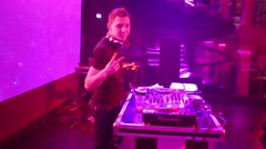 DJ is standing next to his turntable on a stage in club. Stock Footage