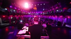 Back view of DJ is standing behind turntable on a stage in Red club. Stock Footage
