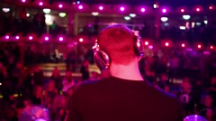 Back view of DJ is standing on a stage in dance club. Stock Footage