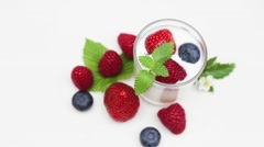 Yogurt with fresh berries and mint leaves isolated Stock Footage
