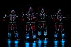 Dancers in led suits on dark background, colored show Stock Photos
