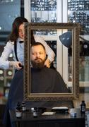 Man having his beard and hair trimmed at a barber - stock photo