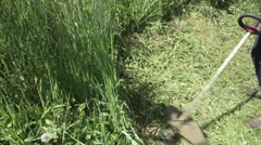 Worker cuts the grass with lawn string trimmer - stock footage