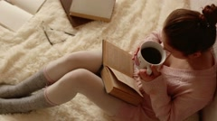 Young woman reading a book and drinking coffee Stock Footage