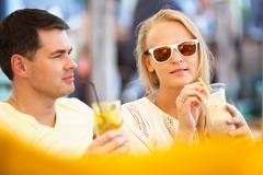 Young couple relaxing with refreshing drinks Stock Photos