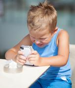 Young boy peering closely at a mobile phone Stock Photos
