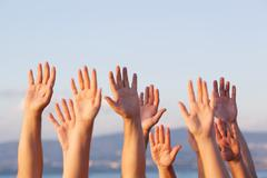 Unrecognizable people pulling hands in the air - stock photo