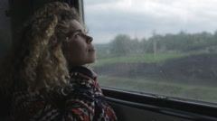 Frizzy woman looking at window in trip by train Stock Footage